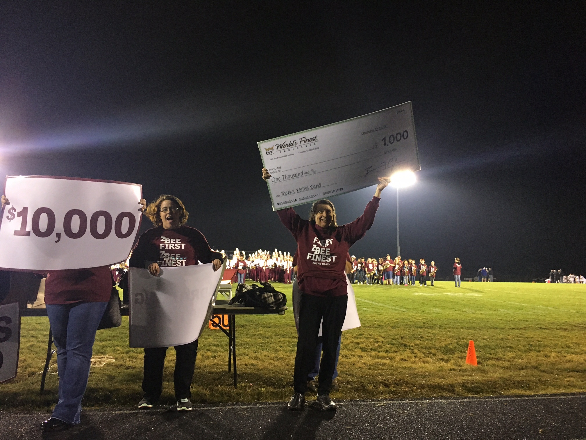Picture: Band booster holding up large $1000 check as a prize for most sales in the fundraiser