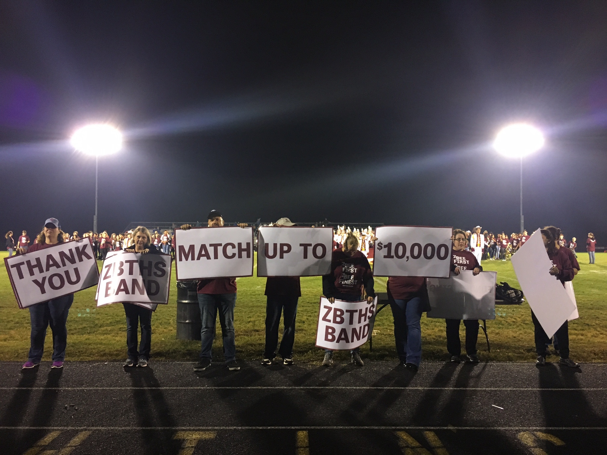 Picture: Band boosters holding up signs about WFC matching $10,000 in their band fundraising effort