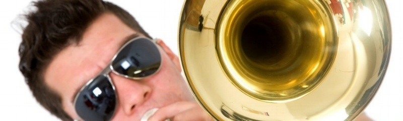 Image: guy playing a trombone while the band director researches band fundraiser ideas